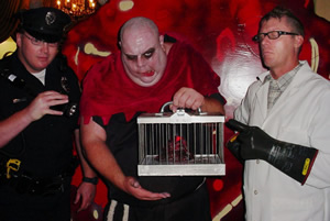 A caged blob held by costumed revelers