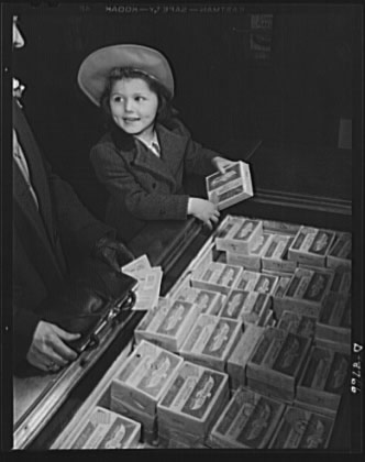 A girl holding frozen food while her mother looks at her ration book in World War II